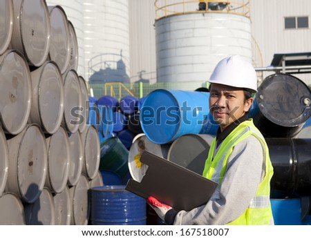 Portrait of a smiling confident supervisor stock  drum checking in warehouse  - stock photo