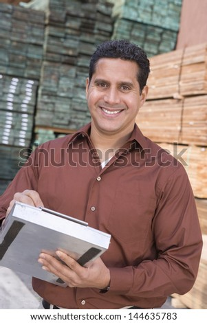Portrait of a smiling confident supervisor stock taking in warehouse - stock photo