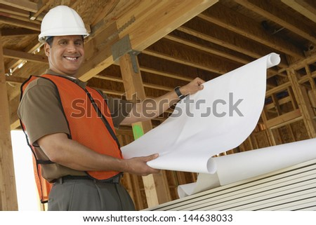 Portrait of a smiling construction worker with blueprints - stock photo