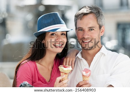 Portrait of a smiling couple eating ice cream in the city. The grey hair man with a beard is in a white shirt. The woman is wearing a blue hat and a pink top. - stock photo