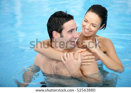 Portrait of a smiling couple in a swimming pool - stock photo