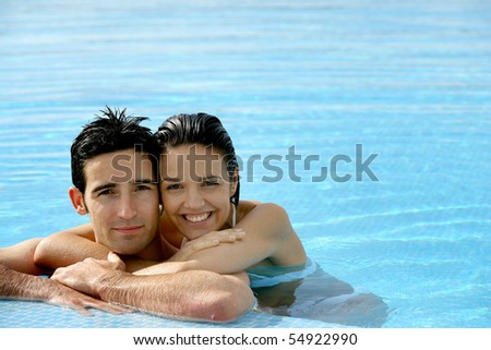 Portrait of a smiling couple leaning on a poolside - stock photo