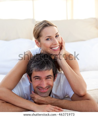 Portrait of a smiling couple lying on the bed - stock photo