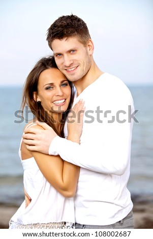 Portrait of a smiling couple posing with the beach as background - stock photo