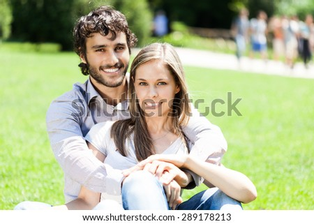 Portrait of a smiling couple relaxing outdoors - stock photo