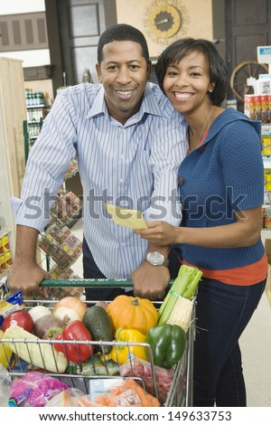 Portrait of a smiling couple standing with grocery shopping in supermarket aisle - stock photo