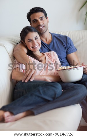 Portrait of a smiling couple watching television while eating popcorn in their living room - stock photo