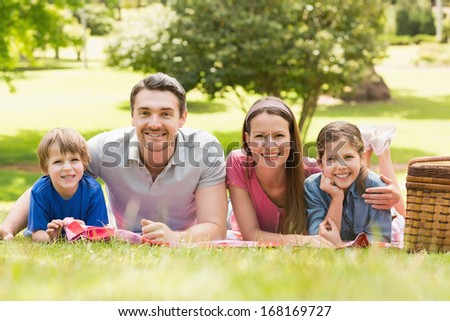 Portrait of a smiling couple with young kids lying on grass in the park - stock photo