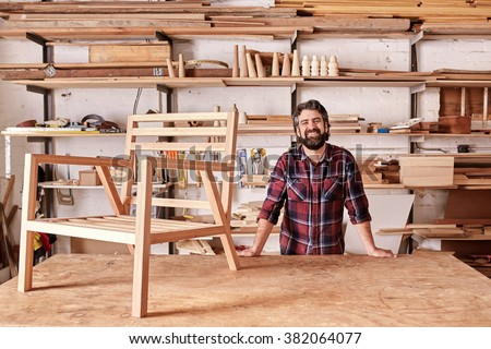 Portrait of a smiling craftsman with a rugged beard, resting on his workbench with a wooden chair frame on it, looking at the camera, with shelves of wooden planks and pieces behind him - stock photo