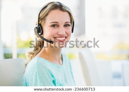 Portrait of a smiling creative businesswoman with earpiece in office - stock photo