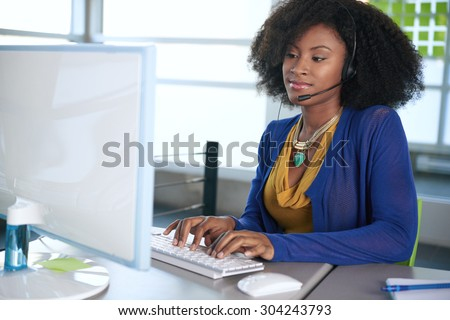 Portrait of a smiling customer service representative with an afro at the computer using headset - stock photo