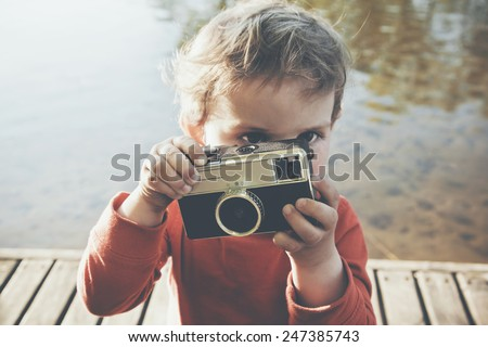 Portrait of a smiling cute boy taking picture with retro camera at a lake - stock photo