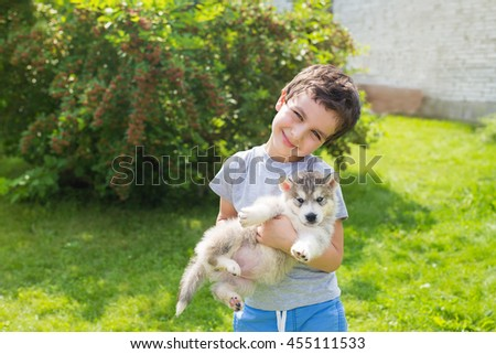 Portrait of a smiling cute little boy with a angry husky puppy - stock photo