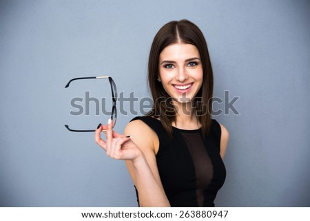 Portrait of a smiling cute woman holding glasses over gray background. Wearing black sexy dress. Looking at the camera. - stock photo