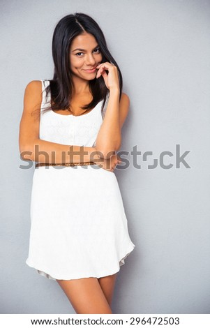 POrtrait of a smiling cute woman standing in trendy white dress over gray background and looking at camera - stock photo
