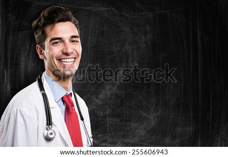 Portrait of a smiling doctor in front of a blackboard - stock photo
