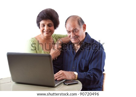 Portrait of a smiling elderly East Indian couple on computer laptop - stock photo
