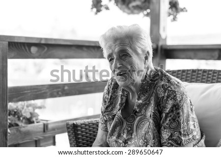 Portrait of a smiling elderly woman - black and white - stock photo