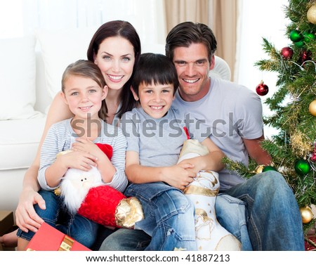 Portrait of a smiling family at Christmas time holding lots of presents at home - stock photo