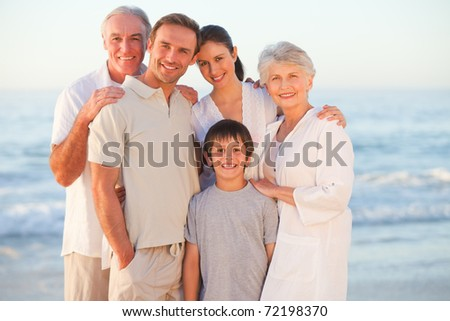 Portrait of a smiling family at the beach - stock photo