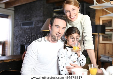 Portrait of a smiling family having breakfast - stock photo
