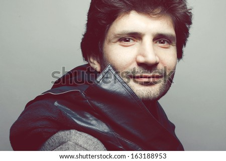 Portrait of a smiling fashionable handsome mature man in gray sweater (pullover) with blue leather jacket on his shoulders posing over blue (green) background. Close up. Studio shot - stock photo