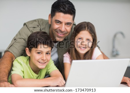 Portrait of a smiling father with young kids using laptop in the kitchen at home - stock photo