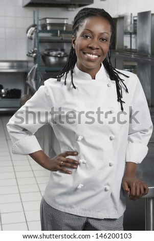 Portrait of a smiling female chef in the kitchen - stock photo