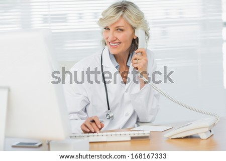 Portrait of a smiling female doctor with computer using phone at medical office - stock photo