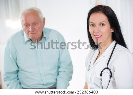 Portrait of a smiling female doctor with senior patient at the medical office - stock photo