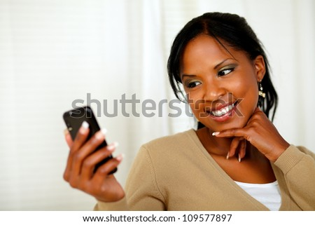 Portrait of a smiling female sending a message by the cellphone at home indoor - stock photo