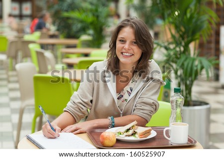 Portrait of a smiling female student doing homework while having breakfast in the cafeteria - stock photo