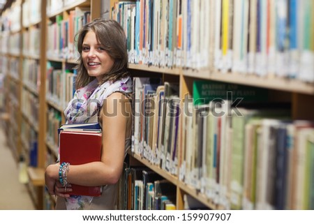 Portrait of a smiling female student leaning against bookshelf in the library - stock photo