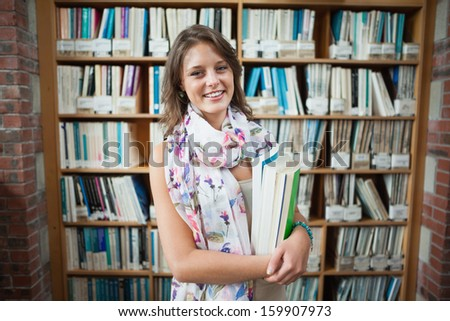 Portrait of a smiling female student standing against bookshelf in the library - stock photo