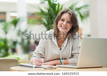 Portrait of a smiling female student writing notes by laptop at cafeteria table - stock photo