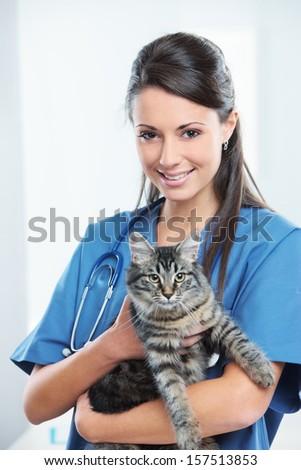 Portrait of a smiling female vet holding a feline  - stock photo