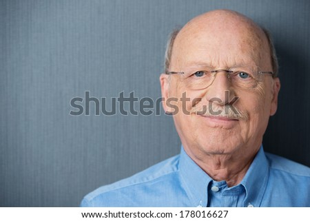 Portrait of a smiling friendly senior man with a moustache wearing glasses on a grey background with copyspace - stock photo
