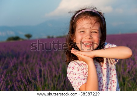 Portrait of a smiling girl in a lavender field - stock photo