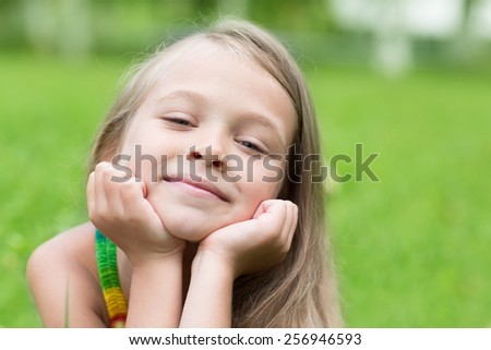 Portrait of a smiling girl in a park. Girl seven years. - stock photo