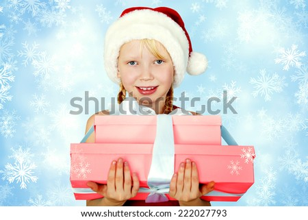 portrait of a smiling girl in a Santa hat with a gift in her hands. Christmas child - stock photo