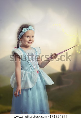 Portrait of a smiling girl in blue dress with a magic wand in her hand, fairy tale landscape on background - stock photo