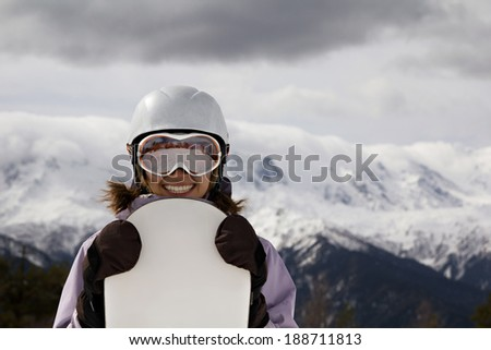 portrait of a smiling girl in helmet and mask with snowboard on snow-capped mountains background - stock photo