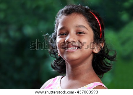 Portrait of a smiling girl of Indian origin in outdoor background - stock photo
