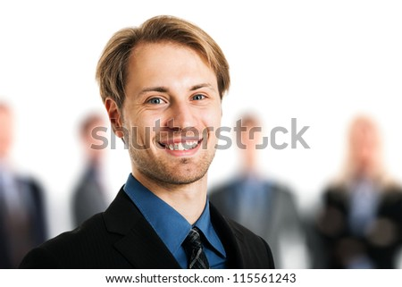 Portrait of a smiling handsome businessman in front of his team - stock photo