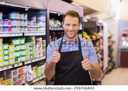 Portrait of a smiling handsome with thumb up in supermarket - stock photo