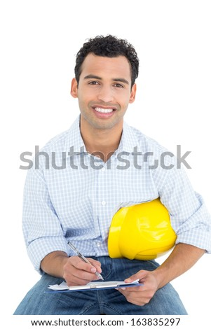 Portrait of a smiling handyman with yellow hard hat writing in clipboard against white background - stock photo