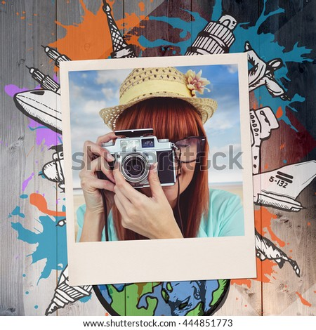 Portrait of a smiling hipster woman holding retro camera against colored wood - stock photo