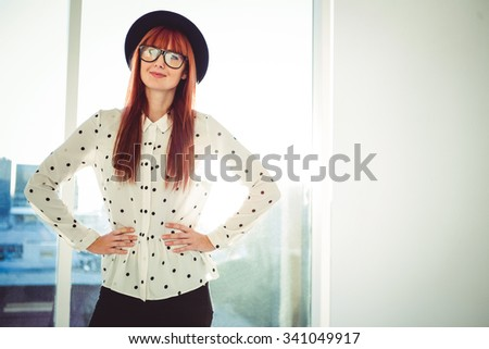 Portrait of a smiling hipster woman with hands on hips in a bright room - stock photo