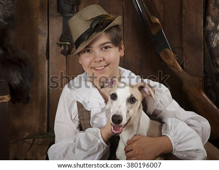 Portrait of a smiling hunter boy hugging his Whippet dog