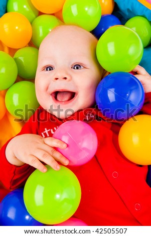 Portrait of a smiling infant lying with colorful balls - stock photo